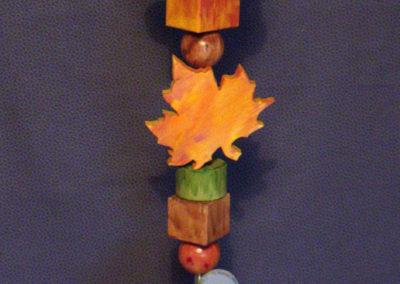 Diese Holzstele (Glückswächter) ist ein echter Blickfang vor bzw. im Haus. Durch die herbstlich bemalten Ahornblätter bringt er etwas Farbe in die dunkle Zeit. Verschiedene Rund- und Kanthölzer, Kugeln und Baumscheiben lockern das ganze auf.