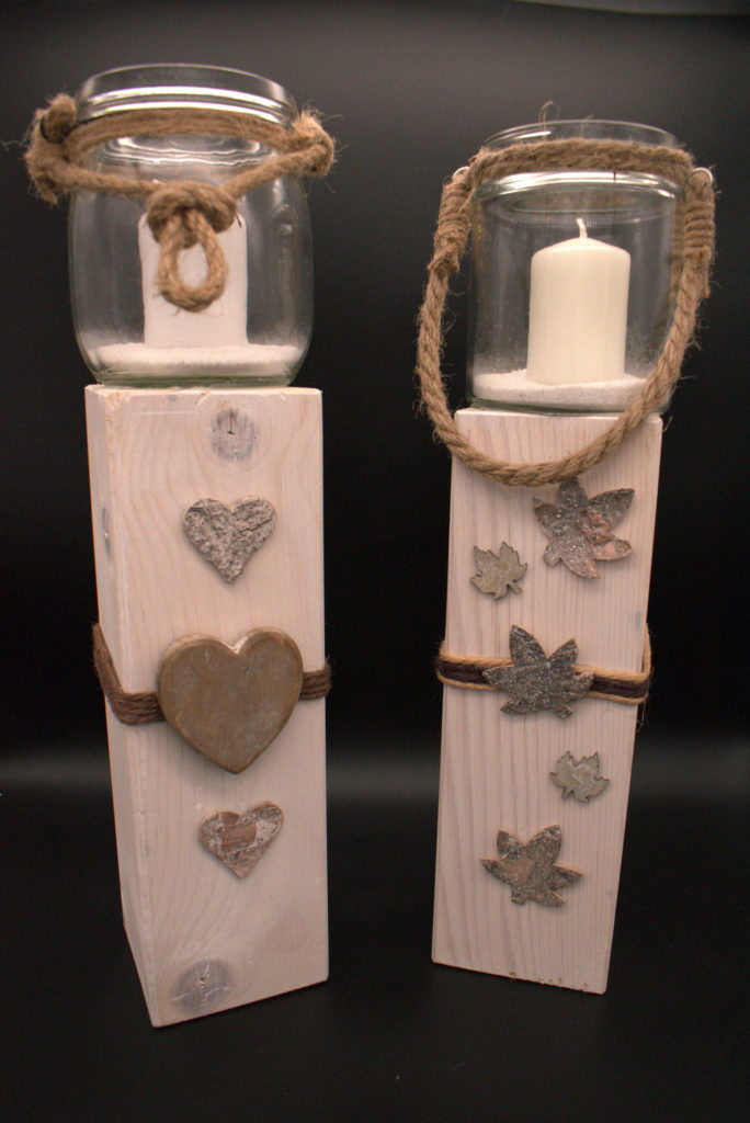 Etwas moderner schlicht in weiß gehalten Windlichtglas mit weißer Kerze. Holzbalken mit Herzen und Blättern dekoriert.