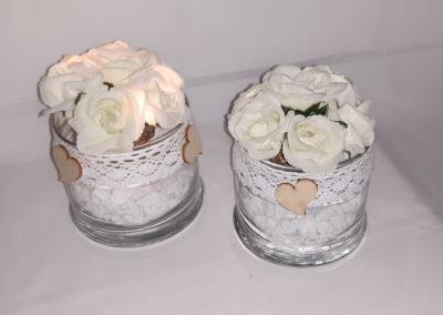 Dekaoratives Glas mit weißen Steinen, Weidenkugel mit weißen Rosenblüten, Lichterketteund Spitzenbordüre
