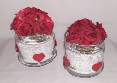 Dekaoratives Glas mit weißen Steinen, Weidenkugel mit roten Rosenblüten und Lichterkette